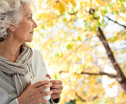 60-letnia kobieta patrząca w okno