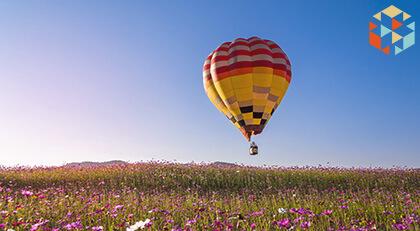 Lot balonem na tle nieba nad łąka pełną kwiatów