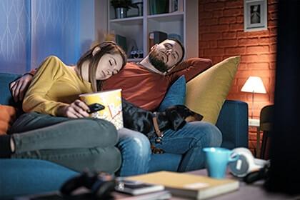 Para śpiąca na kanapie przed telewizorem