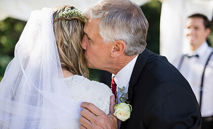 Ojciec składający życzenia i całujący Pannę Młodą w dniu ślubu