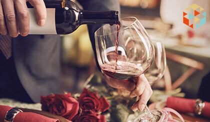 Kelner nalewa czerwone wino z butelki do kieliszka podczas eleganckiej kolacji w restauracji