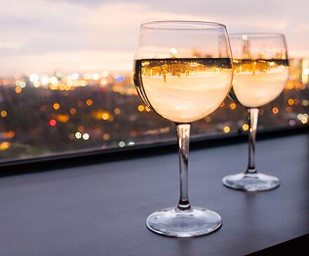 Kieliszki z winam stojące na parapecie z panoramą miasta z tyłu