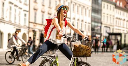 Kobieta jadąca na rowerze w przez miasto