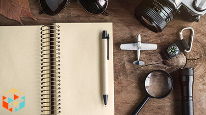 Drewniany blat z notatnikiem i akcesoriami podróżnika - lornetka, szkoło powiększające