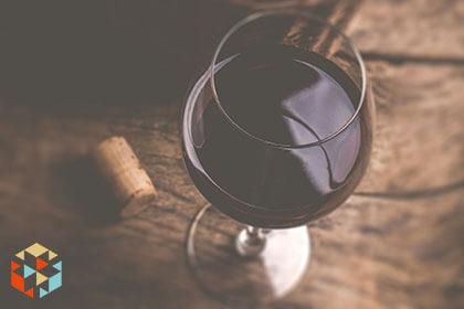 Kieliszek czerwonego wina na drewnianym stole