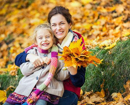 Matka z córką podczas spaceru w parku wśród liści