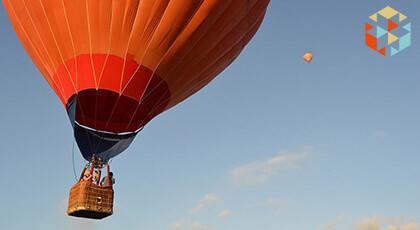 Lecący pomarańczowy balon na tle niebieskiego nieba