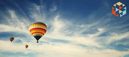 Kolorowy balon na gorące powietrze lacący na tle błękitnego nieba