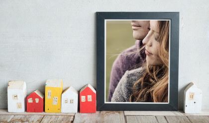 Obraz przedstawiający parę zakochanych ludzi oprawiony w ramę i oparty o ścianę