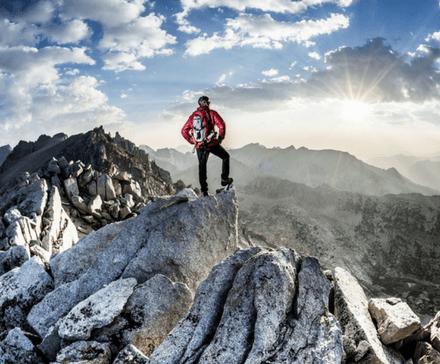 Mężczyzna na wierzchołgu wysokiej góry