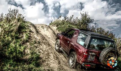 Samochód terenowy pokonujące wzniesienie trudnego piaszczystego terenu