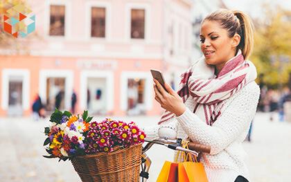 Kobieta z rowerem i koszem kwiatów czyta wiadomość z telefonu