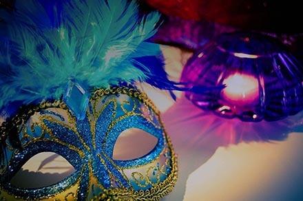 Maski tetralne zdobione kolorowymi pióramia leżące na stole
