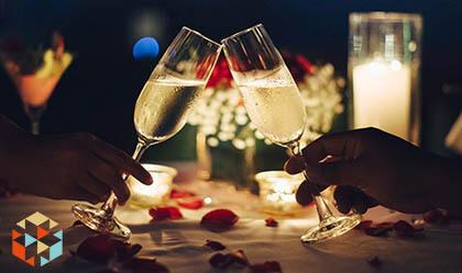 Kieliszki z winem podnoszone do góry podczas romantycznej kolacji