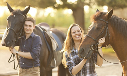 Kobieta i mężczyzna przygotowujący sie do jazdy konnej