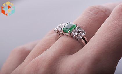 Pierscionek zaręczynowy ze szlachetnymi kamieniami na palcu